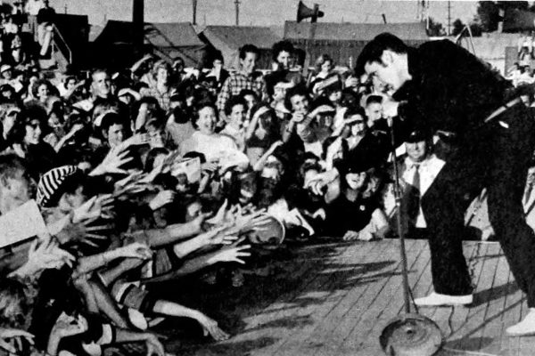 An Elvis Presley Signature Scarf was worn at his love shows and concerts. They were Given to fans by the king himself to lucky fans. Elvis Presley reaching out to fans during a live show on stage.
